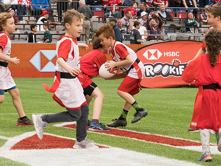 Children playing a game of tag rugby in an HSBC Rookie Rugby programme
