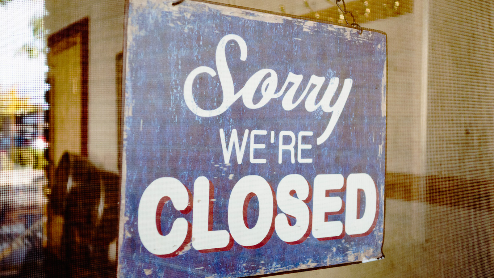 "A sign saying ""we are closed"" hangs in the window of a shop"