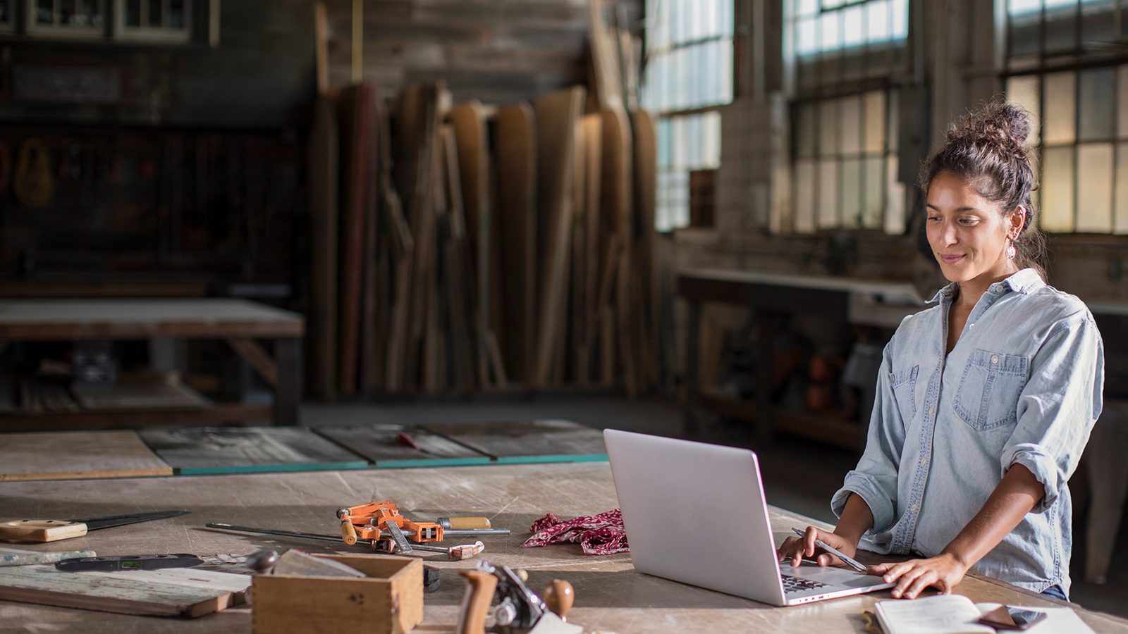 Young Mixed Race Female Entrepreneur Solving a Complicated Business Challenge with Pencil, Laptop, Carpentry Tools, and Confidence