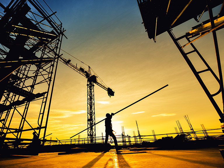 A worker on a construction site at sunset