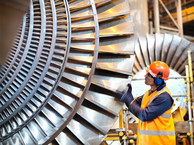 A worker inspects a turbine in a power station