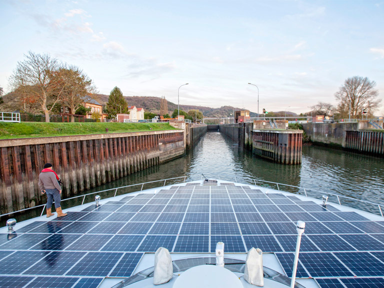 A boat covered with solar panels in a canal