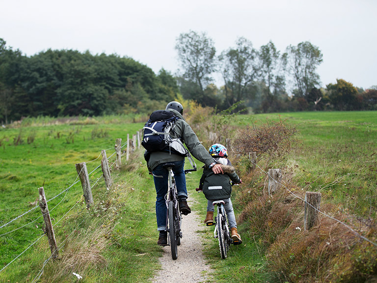 Father and son cycling together in nature