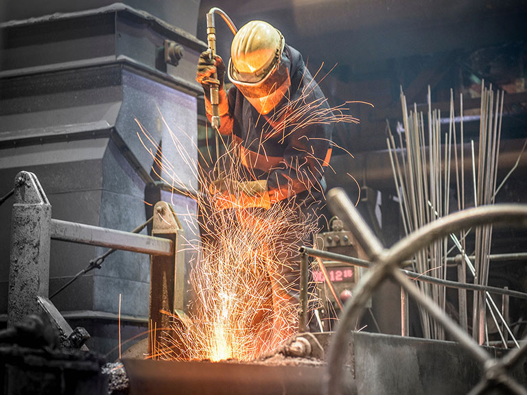 A steel worker and sparks from molten steel in an industrial foundry
