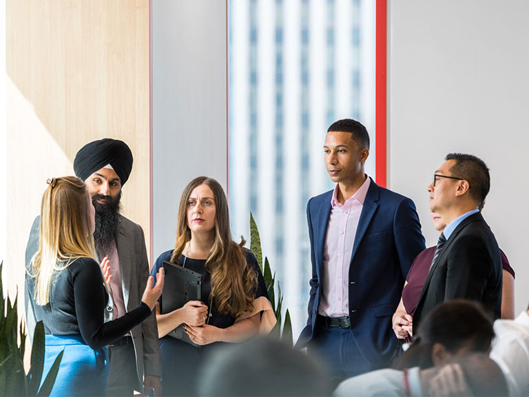 A group of six HSBC employees talk together